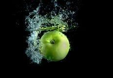 Grüner Apfel mit spritzt Lizenzfreie Stockbilder