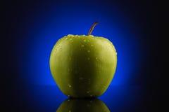 Grüner Apfel mit Tropfen auf blauem Hintergrund Stockfoto