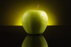 Grüner Apfel mit Tropfen auf gelbem Hintergrund Lizenzfreie Stockbilder