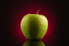 Grüner Apfel mit Tropfen auf rotem Hintergrund Stockfotografie