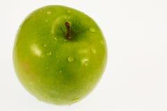 Grüner Apfel mit Wassertropfen Stockfotografie