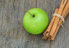 Grüner Apfel mit Zimt auf hölzernem Hintergrund Lizenzfreie Stockfotos
