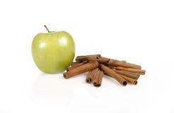 Grüner Apfel mit Zimtsteuerknüppeln Stockfoto