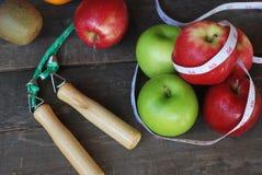 Grüner Apfel, roter Apfel Konzeptdiät auf einem Bretterboden stockbilder