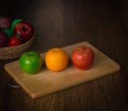 Grüner Apfel, roter Apfel und Orange auf Hackklotz und Früchte in einem Korb auf Schreibtischhintergrund Lizenzfreie Stockbilder