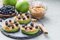 Grüner Apfel rundet mit Erdnussbutter und Blaubeeren auf Schiefer verschalen, horizontal, kopieren Raum Lizenzfreie Stockfotos