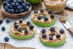Grüner Apfel rundet mit Erdnussbutter und und Blaubeeren auf dem Holztisch, horizontal Lizenzfreie Stockfotos