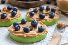 Grüner Apfel rundet mit Erdnussbutter und und Blaubeeren auf dem Holztisch, horizontal Lizenzfreies Stockbild