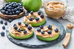 Grüner Apfel rundet mit Erdnussbutter und und Blaubeeren auf Schiefer verschalen, horizontal Lizenzfreie Stockfotos