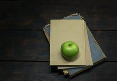 Grüner Apfel und alte Bücher Lizenzfreie Stockfotos