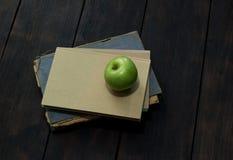 Grüner Apfel und alte Bücher Stockfoto