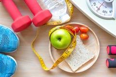 Grüner Apfel und Gewichtsskala, Maßhahn mit Trinkwasser und Sportausrüstung für Frauen nähren das Abnehmen Lizenzfreies Stockfoto