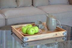 Grüner Apfel und keramische Schale in hölzernem tary auf Glasplattetabelle Stockbild