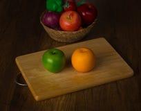 Grüner Apfel und Orange auf Hackklotz und Früchte in einem Korb auf Schreibtischhintergrund Stockbild