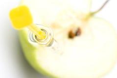 Grüner Apfel und Spritze Stockbild