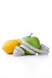 Grüner Apfel und Zitrone mit dem messenden Band lokalisiert auf weißem Hintergrund Lizenzfreies Stockfoto