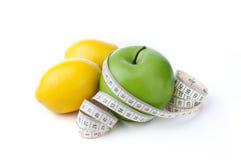 Grüner Apfel und Zitrone mit dem messenden Band lokalisiert auf weißem Hintergrund Lizenzfreie Stockfotografie