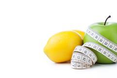 Grüner Apfel und Zitrone mit dem messenden Band lokalisiert auf weißem Hintergrund Stockbild