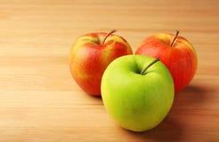 Grüner Apfel unter Rot eine Stockbild