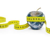 Grüner Apfel wickelte das messende Band auf einem weißen Hintergrund ein Lizenzfreies Stockbild