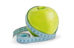 Grüner Apfel wird in einem messenden Band eingewickelt Stockfotografie