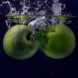 Grüner Apfel zwei unter Wasser mit einer Spur von transparenten Blasen stockbild