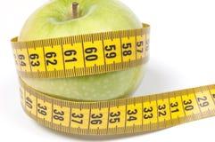 Grüner Apple mit dem messenden Band, getrennt auf Weiß Lizenzfreie Stockbilder