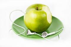 Grüner Apple mit Kopfhörern auf grüner Platte stockfotografie