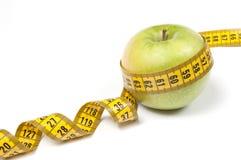 Grüner Apple mit messendem Band Stockbilder