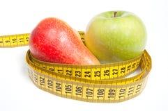 Grüner Apple und Birne mit messendem Band Stockfotografie