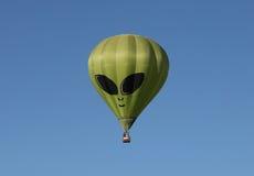 Grüner ausländischer Heißluft-Ballon gegen einen blauen Himmel Stockbild