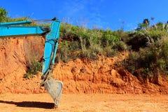 Grüner Bagger, der den Boden auf Baustelle gräbt Lizenzfreies Stockfoto