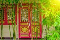 Grüner Bambus mit Hintergrund der chinesischen Art der Unschärfearchitekturtür Lizenzfreie Stockfotos