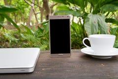 Grüner begrifflicharbeitsplatz, beweglich mit leerem Bildschirm auf Tabelle, Kaffeetasse und grünem Gartenhintergrund, Geschäftst stockfoto