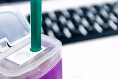 Grüner Bleistift in einem purpurroten Bleistiftspitzer auf Laptophintergrund Lizenzfreie Stockfotos