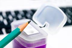Grüner Bleistift in einem purpurroten Bleistiftspitzer auf Laptophintergrund Stockfoto