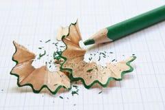 Grüner Bleistift und Bleistiftschnitzel auf Notizbuch Lizenzfreie Stockbilder