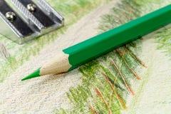 Grüner Bleistift und Bleistiftspitzer auf dem Hintergrund des Bildes Lizenzfreie Stockbilder