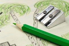Grüner Bleistift und Bleistiftspitzer auf dem Hintergrund von Kind-` s Zeichnung Stockbilder