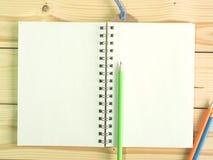 Grüner Bleistift und leeres Buch auf hölzernem Schreibtisch Stockfotos