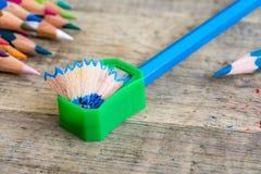Grüner Bleistiftspitzer auf hölzernem Hintergrund Lizenzfreies Stockfoto