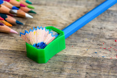 Grüner Bleistiftspitzer auf hölzernem Hintergrund Stockbild