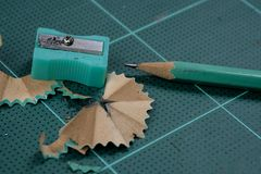 Grüner Bleistiftspitzer ist auf der grünen Ausschnittplatte mit Bleistift Lizenzfreies Stockfoto