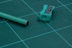Grüner Bleistiftspitzer ist auf der grünen Ausschnittplatte mit Bleistift Lizenzfreies Stockbild