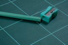 Grüner Bleistiftspitzer ist auf der grünen Ausschnittplatte mit Bleistift Lizenzfreie Stockfotos