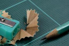 Grüner Bleistiftspitzer ist auf der grünen Ausschnittplatte mit Bleistift Stockfotos