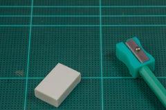 Grüner Bleistiftspitzer ist auf der grünen Ausschnittplatte mit Radiergummi Lizenzfreie Stockfotos
