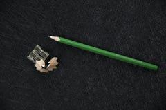 Grüner Bleistiftspitzer und geschärfter Abfall stockbild