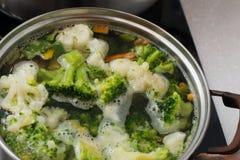 Grüner Brokkoli ist in der Wanne in kochendem Wasser lizenzfreie stockbilder