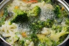 Grüner Brokkoli ist in der Wanne in kochendem Wasser stockfoto